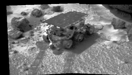 The image on Mars was taken by NASA's Imager for Mars Pathfinder (IMP) on July 8, 1997. The rover Sojourner has traveled to an area of soil and several rocks. Its tracks are clearly visible in the soft soil seen in the foreground.