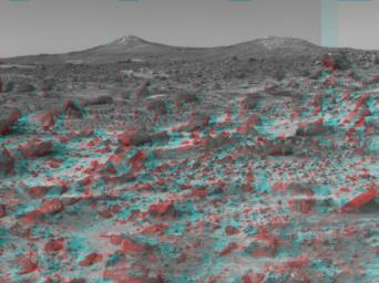 The two hills in the distance in this stereo image from NASA's Mars Pathfinder have been dubbed the 'Twin Peaks.' 3D glasses are necessary to identify surface detail.