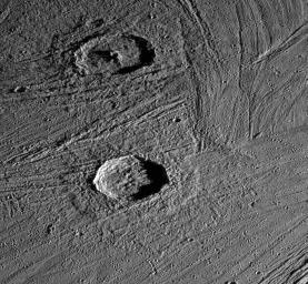 This image captured by NASA's Galileo spacecraft shows an oblique view of two fresh impact craters in bright grooved terrain near the north pole of Jupiter's moon, Ganymede.