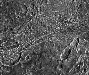 This image captured by NASA's Galileo spacecraft shows dark terrain of Nicholson Regio on Jupiter's moon, Ganymede. On the left is a crater that has been torn apart by tectonic forces.
