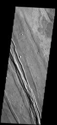 The linear features in this image are called graben and are formed when  two parallel faults have a downdropped block of material between them.  These graben are located between Syria Planum and Claritas Rupes