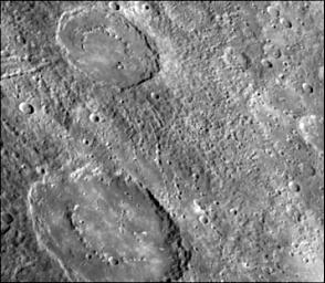 The craters in this image NASA's Mariner 10 spacecraft, which launched in 1974, have interior rings of mountains and ejecta deposits which are scarred by deep secondary crater chain groves.