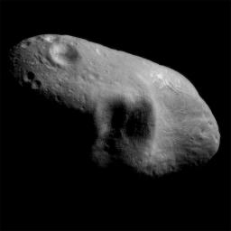 This image from NASA's NEAR Shoemaker shows asteroid Eros' saddle and a shadowed feature to its left, taken on March 3, 2000 from a distance of 127 miles. A shadowed feature that consists of three large craters are situated adjacent to each other.
