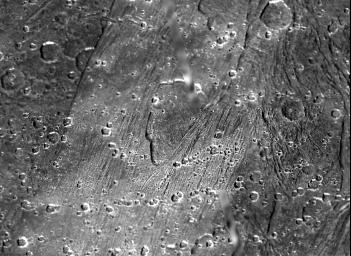 The shallow, scalloped depression in the center of this picture from NASA's Galileo spacecraft is a caldera-like feature 5 to 20 kilometers (3 to 12 miles) wide on Jupiter's largest moon, Ganymede.
