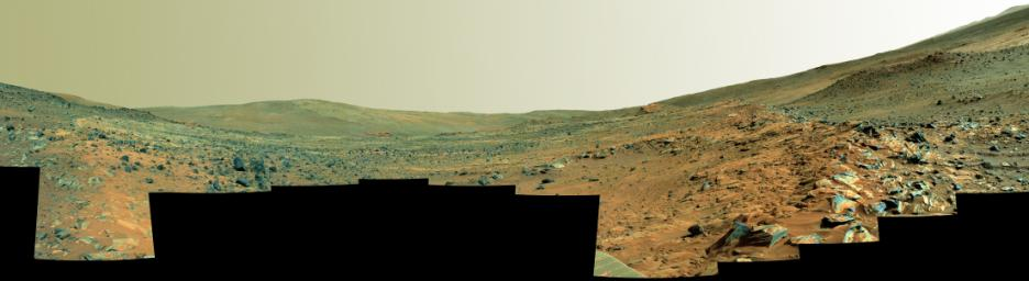 This panorama shows two rock-strewn slopes on the left and right sides of a broad, U-shaped dip in the middle. The sandy surface in front of the rover is reddish brown; individual rocks and more distant features are blue-gray