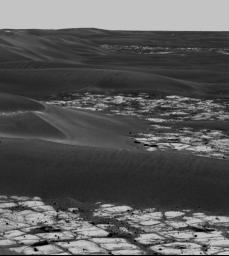 This image, taken Oct. 9, 2005 by NASA's rover Opportunity, is a portion of a mosaic that highlights the light-toned outcrop on the rim of 'Erebus Crater' and large, dark, wind-deposited drifts that have filled the center of the crater.