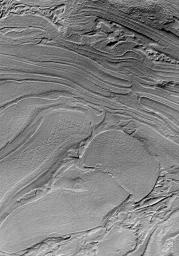 NASA's Mars Global Surveyor shows a jumble of plates or layers exposed at the surface but subsequently covered by a thin mantle to give northwestern Hellas Planitia on Mars a uniform brightness.