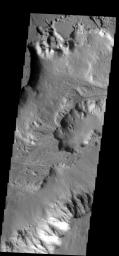 This image shows part of Shalbatana Vallis, with steep cliffsides and  large pit in the channel floor. Many small channels appear to end at the  pit, or pass to its north