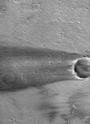 NASA's Mars Global Surveyor shows a dark wind streak formed in the lee of a crater in Daedalia Planum on Mars.