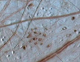 Reddish spots and shallow pits pepper the enigmatic ridged surface of Europa in this view combining information from images taken by NASA's Galileo spacecraft during two different orbits around Jupiter.