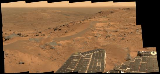 This mini-panorama was taken by NASA's Spirit rover on August 23, 2005, just as the rover finally completed its intrepid climb up Husband Hill. The summit shows a windswept plateau of scattered rocks, little sand dunes and small exposures of outcrop.