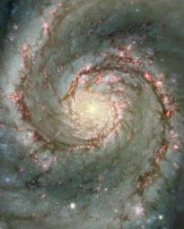 The image from NASA's Hubble Telescope shows spiral arms and dust clouds in the nearby Whirlpool galaxy. Visible starlight and light from the emission of glowing hydrogen is seen, which is associated with the most luminous young stars in the spiral arms.