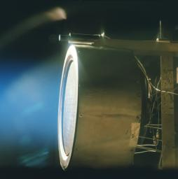 This image of a xenon ion engine prototype, photographed through a port of the vacuum chamber where it was being tested at NASA's Jet Propulsion Laboratory, shows the faint blue glow of charged atoms being emitted from the engine.