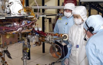 JPL engineers examine the robotic arm of NASA's Mars Exploration Rover 1.