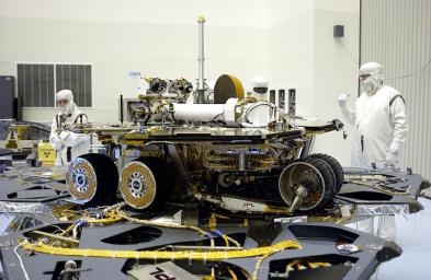 In the Payload Hazardous Servicing Facility, the lander petals of the Mars Exploration Rover 2 (MER-2) have been reopened and its solar panels deployed to allow technicians access to the spacecraft to remove one of its circuit boards.