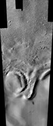 This image from NASA's 2001 Mars Odyssey released on Dec 8, 2003 shows remarkable layered deposits covering older, cratered surfaces near Mars' south pole. The margin of these layered deposits appears to be eroding poleward.