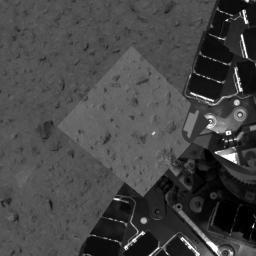 This image taken by the panoramic camera onboard NASA's Mars Exploration Rover Spirit highlights the first patch of soil examined by the rover's microscopic imager. The rover can be seen to the right.