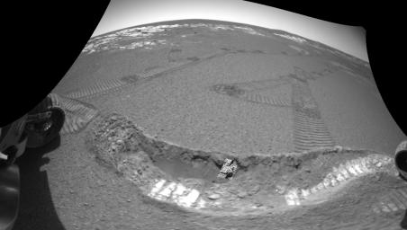 NASA's Mars Exploration Rover Opportunity shows the crater floor at Meridiani Planum, Mars, after the rover dug a trench on Feb. 16, 2004. A small patch of soil is seen in the center of the trench wall with the rovers' tracks leading off in the distance.