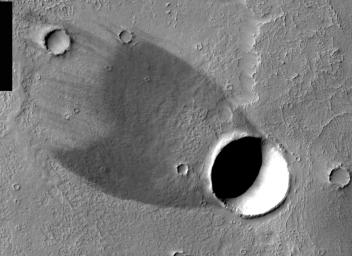 This image, part of an images as art series from NASA's 2001 Mars Odyssey released on Feb 24, 2004 shows that winds blowing over a crater's rim have scoured the ground behind the crater free of light-colored dust, exposing a relatively bare lava flow.