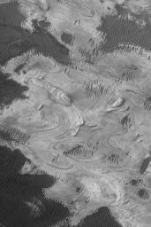 NASA's Mars Global Surveyor shows exposures of finely-bedded sedimentary rocks in western Melas Chasma, part of the vast Valles Marineris trough system on Mars.