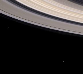 This image from NASA's Cassini spacecraft shows Saturn's colorful rings sweep through this spectacular natural color view while two small moons look on.