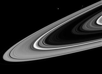 As NASA's Cassini spacecraft swung around to the dark side of the planet during its first close passage after orbit insertion, the intrepid spacecraft spied three ring moons whizzing around the planet.