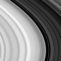 This image NASA's Cassini spacecraft shows subtle, wavelike patterns, hundreds of narrow features resembling a record's 'grooves' in Saturn's outer B-ring, and a noticeable abrupt change in overall brightness beyond the dark gap near the right.