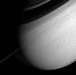 Saturn's whirling vortices and feathery cloud bands are the signs of a restless world. NASA's Cassini spacecraft captured this arresting view of the giant planet scored by bold shadows cast by the rings.