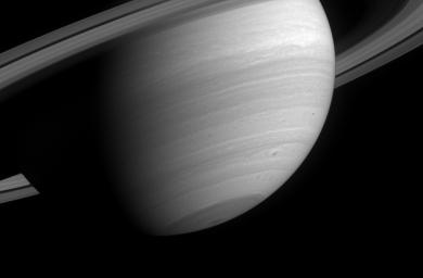This poetic wide-angle camera view of Saturn reveals several small, dark storms in the southern latitudes, where storm activity has been prevalent since before NASA's Cassini spacecraft arrived in orbit.