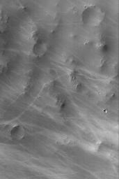 NASA's Mars Global Surveyor shows wild patterns of dark streaks thought to have formed by the passage of many dust devils. The dust devils disrupt the dust coating the martian surface, leaving behind a streak.