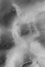 NASA's Mars Global Surveyor shows old, light-toned, large ripples on a smoothly mantled surface in the Sinus Sabaeus region, south of Schiaparelli Basin on Mars.