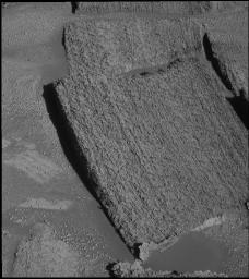 This image from NASA's Mars Exploration Rover Opportunity taken Dec. 3, 2004, shows light rocks and dark rocks along the rim of 'Endurance Crater' on Mars. The pictured rock, 'Tipuna,' lies just under the dividing line, in the dark section.