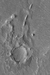 NASA's Mars Global Surveyor shows layered outcrops of sediment deposited in southern Chryse Planitia by flow through the Hypanis Valles system in Xanthe Terra on Mars. The distinct inverted boat hull-shaped ridges are yardangs formed by wind erosion.