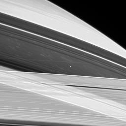 Saturn's shepherd moon Prometheus hovers between the A and F rings as if suspended on an invisible thread, while bright clouds drift in Saturn's atmosphere approximately 130,000 kilometers beyond. This image was captured by NASA's Cassini spacecraft.