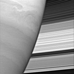 Turbulent swirls churn in Saturn's atmosphere while the planet's rings form a dazzling backdrop. The rings' complex structure is clearly evident in this view captured by NASA's Cassini spacecraft.