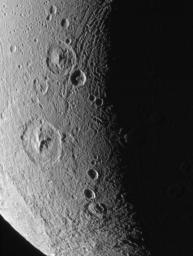This close-up of Saturn's moon Dione's icy surface shows deeply shadowed craters near the terminator, as well as a group of roughly linear faults above center. This image was taken by NASA's Cassini spacecraft on Dec. 24, 2005.