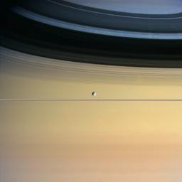 Cool and icy Dione floats in front of giant Saturn bedecked in a dazzling  array of colors