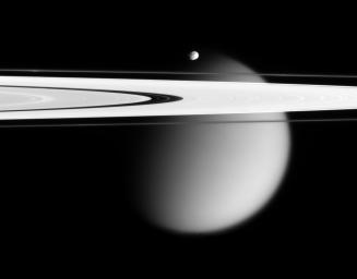 The Cassini spacecraft delivers this stunning vista showing small,  battered Epimetheus and smog-enshrouded Titan, with Saturn's A and F  rings stretching across the scene