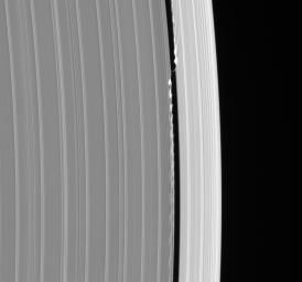 Daphnis, the tiny moon that inhabits the Keeler Gap in the outer edge of Saturn's A ring, is captured here in remarkable detail with its entourage of waves. This image was taken in visible light with NASA's Cassini spacecraft's narrow-angle camera.