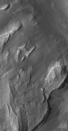 NASA's Mars Global Surveyor shows outcroppings of layered, sedimentary rock in eastern Gale Crater on Mars. North-central Gale Crater is the site of a mound that is more than several kilometers thick and largely composed of sedimentary rocks.