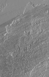 NASA's Mars Global Surveyor shows dark wind streaks streaming across lava flow surfaces in eastern Tharsis, west of the Kasei Valles region of Mars.
