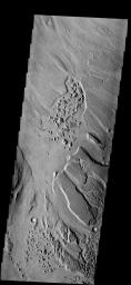 The patches of chaotic material in this image have formed on the floor of  Mangala Valles