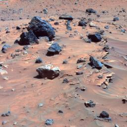 This false-color image shows paper-thin layers of light-toned, jagged-edged rocks; a light gray rock with smooth, rounded edges atop and drifts; and several dark gray to black, angular rocks with vesicles typical of hardened lava scattered across the sand