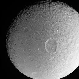 This dramatic close-up of Tethys shows the large crater Penelope lying  near center, overprinted by many smaller, younger impact sites