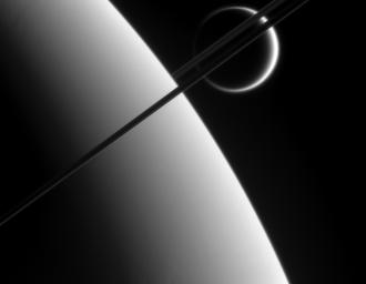 This view was taken from above the ringplane and looks toward the unlit side of the rings. Here, the probe gazes upon Titan in the distance beyond Saturn and its dark and graceful rings