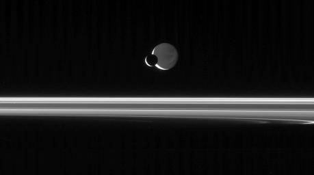 The Cassini spacecraft looks across the unlit ringplane as Mimas glides  silently in front of Dione
