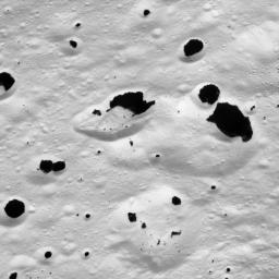 Dark material splatters the walls and floors of craters in the surreal, frozen wastelands of Iapetus as seen by NASA's Cassini spacecraft on Sept. 10, 2007.