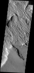 This image has a cracked plateau of material next to a low region of interconnected small ridges. This region is located at the northwestern end of Gordii Dorsum