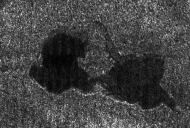 This Cassini radar image shows two lakes 'kissing' each other on the surface of Saturn's moon Titan. The image from a flyby on Sept. 23, 2006, covers an area about 60 kilometers (37 miles) wide by 40 kilometers (25 miles) high.