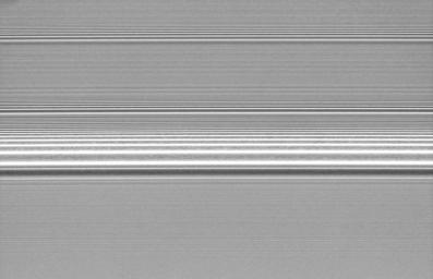 Several spiral density waves in Saturn's A ring are seen in this detailed view from NASA's Cassini spacecraft. There is a grainy texture visible between the brightness peaks in the most prominent wave.